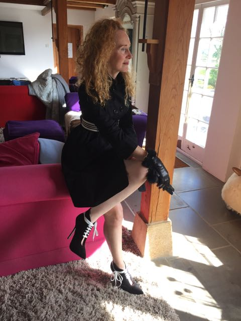 Burberry raincoat, fur trimmed gloves, black leather gloves, high heeled ankle boots, red curly hair, country house interior